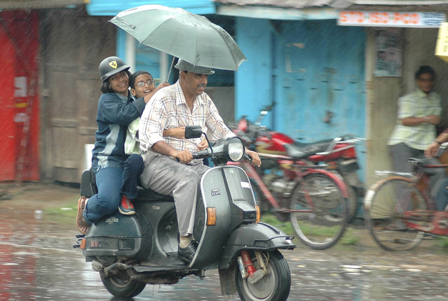 A family rides on a scooter during a monsoon shower in Agartala, June 16, 2007. (Photo by Jayanta Dey/Reuters)