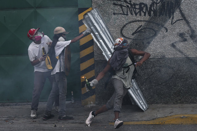 An anti-government protesters throws a molotov bomb at security forces in Caracas, Venezuela, Wednesday, April 19, 2017. (Photo by Fernando Llano/AP Photo)