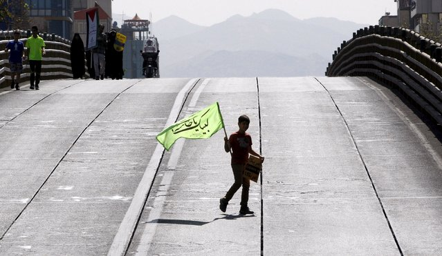 An Iranian boy carries a flag during a rally marking al-Quds (Jerusalem) Day in Tehran July 10, 2015. (Photo by Reuters/Stringer/TIMA)