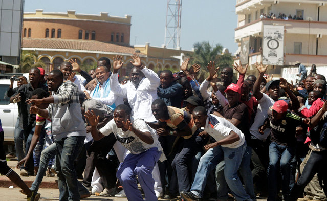 Democratic Republic of Congo's opposition Presidential candidate Moise Katumbi and his supporters react as riot police fire teargas at them as they walk to the prosecutor's office over government allegations he hired mercenaries in a plot against the state, in Lubumbashi, the capital of Katanga province of the Democratic Republic of Congo, May 13, 2016. (Photo by Kenny Katombe/Reuters)