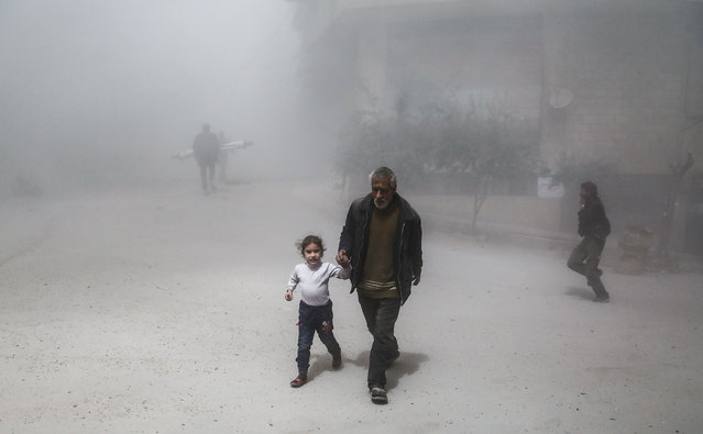 A Syrian man and girl flee following a reported government air strike on the rebel- controlled town of Hamouria, in the eastern Ghouta region on the outskirts of the capital Damascus, on April 4, 2017. (Photo by Abdulmonam Eassa/AFP Photo)