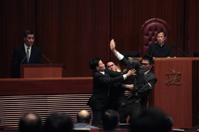 """Pro-democracy lawmaker Leung Kwok-hung (3rd R), also known as """"Long Hair,"""" is blocked by security guards as he tries to approach Hong Kong Chief Executive Leung Chun-ying (L) inside the Legislative Council in Hong Kong, December 10, 2012. At right is Legislative Council Chairman Jasper Tsang. (Photo by Bobby Yip/Reuters)"""