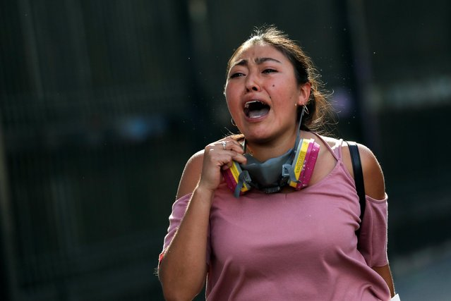 A woman reacts during an anti-government protests in Santiago, Chile on October 28, 2019. (Photo by Henry Romero/Reuters)
