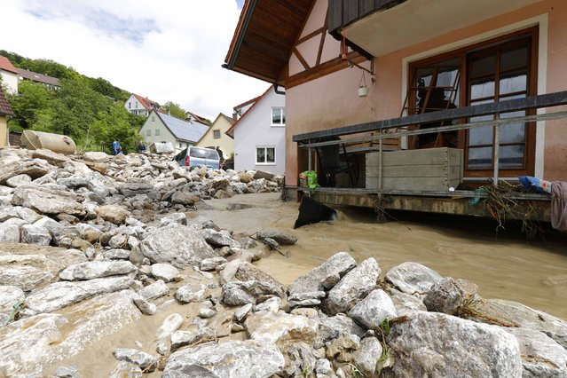 Debris lines a road in front of houses following flooding in the town of Braunsbach, in Baden-Wuerttemberg, Germany, May 30, 2016. (Photo by Kai Pfaffenbach/Reuters)
