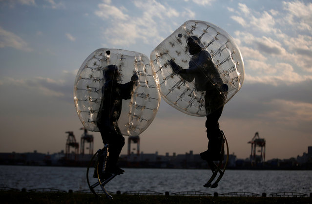 """Ryoichi Ando (R), 27, a virtual-reality researcher and an inventor of """"Bubble Jumper"""", competes with his opponent as they demonstrate the sport in Tokyo, Japan, April 13, 2017. Ando said he felt as if he were wearing the kind of augmented body suit found in science-fiction movies that boosts the wearer's strength. In """"Bubble Jumper"""", players walking on stilts and wearing inflatable bubble protectors crash into each other like sumo wrestlers. (Photo by Kim Kyung-Hoon/Reuters)"""