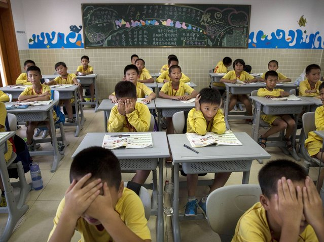 Young Chineseattend classes after training at the Evergrande International Football School near Qingyuan in Guangdong Province. (Photo by Kevin Frayer/Getty Images)