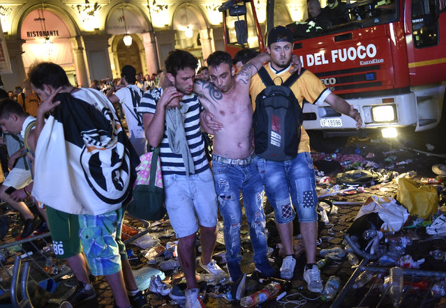 A Juventus fan is helped to walk as the fans gathered in San Carlo Square run away following panic created by the explosion of firecrackers as they was watching the match on a giant screenon on June 3, 2017 in Turin. (Photo by Giorgio Perottino/Reuters)