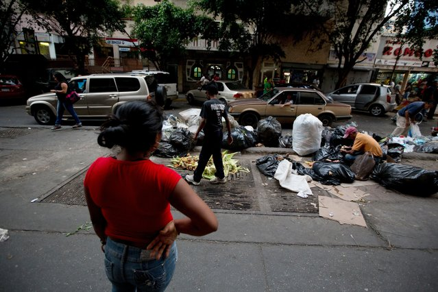 In this May 31, 2016 photo, a young man rummages through a pile of supermarket garbage bags looking for food at downtown Caracas, Venezuela. Unemployed people converge every dusk at the trash heap to pick through rotten fruit and vegetables tossed out by nearby shops. (Photo by Fernando Llano/AP Photo)