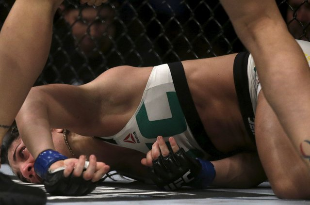Bethe Correia of Brazil lies on the ground after receiving a punch of Ronda Rousey of U.S during the Ultimate Fighting Championship (UFC) match, a professional mixed martial arts (MMA) competition in Rio de Janeiro, Brazil August 1, 2015. (Photo by Ricardo Moraes/Reuters)