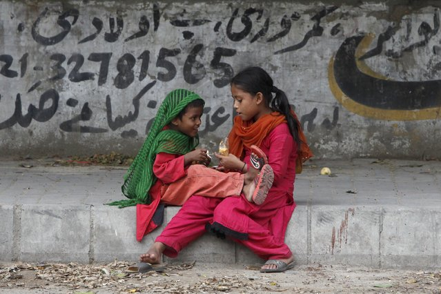 Siblings eat donated food, which they received from a nearby market, along a side walk in Karachi, Pakistan, July 31, 2015. (Photo by Akhtar Soomro/Reuters)