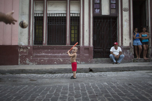 Carlos Ortega Ponce, 3, plays baseball with his father in front of his home in Havana, October 16, 2014. (Photo by Alexandre Meneghini/Reuters)