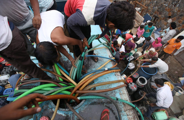 Indian people fill up canisters and containers with water from a tanker in New Delhi, India, 30 July 2015. According to a news report, around 20 per cent of Delhi's population do not have access to water supplied by pipes and are forced to rely on tankers providing water for personal use. The reported difference between water available for the population and what is needed is more than 750 million litres a day. (Photo by Rajat Gupta/EPA)