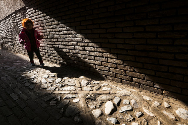 An Afghan girl walks through the old part of the city in Herat, Afghanistan, 21 December 2014. (Photo by Jalil Rezayee/EPA)