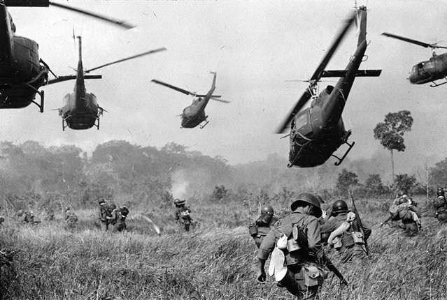 In this March 1965 photo, hovering U.S. Army helicopters pour machine gun fire into the tree line to cover the advance of South Vietnamese ground troops in an attack on a Viet Cong camp 18 miles north of Tay Ninh, Vietnam, northwest of Saigon near the Cambodian border