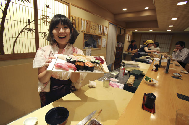 "In this August 3, 2015 photo, Yuki Chidui, sushi chef and manager at Nadeshico sushi restaurant, shows off a set of sushi she made at her all-women restaurant in Tokyo. Deeply rooted stereotypes such as the so-called ""Edo-style"" macho demeanor of sushi chefs and belief that warmer body temperature of women leads to inferior taste have kept sushi preparation an almost exclusively male domain in Japan. (Photo by Koji Sasahara/AP Photo)"
