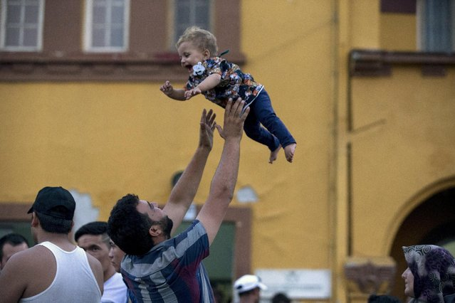 A migrant plays with his child as they wait for a train to arrive at Gevgelija train station in Macedonia, close to the border with Greece, August 14, 2015. (Photo by Stoyan Nenov/Reuters)