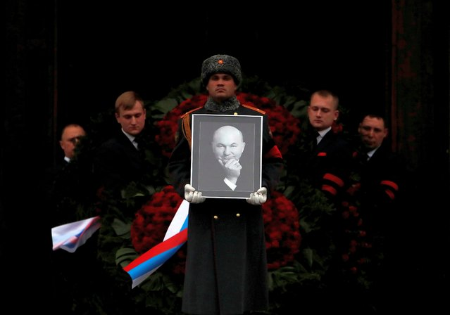 Pallbearers carry the coffin and a portrait of former mayor of Moscow Yuri Luzhkov out of the the Cathedral of Christ the Saviour after a memorial service, in Moscow, Russia on December 12, 2019. (Photo by Maxim Shemetov/Reuters)