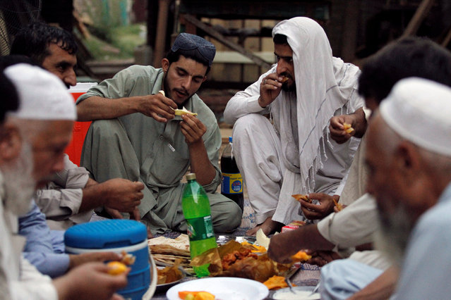 Workers and neighbours of a carpentry workshop break fast during the holy month of Ramadan in Islamabad, Pakistan June 11, 2016. (Photo by Caren Firouz/Reuters)