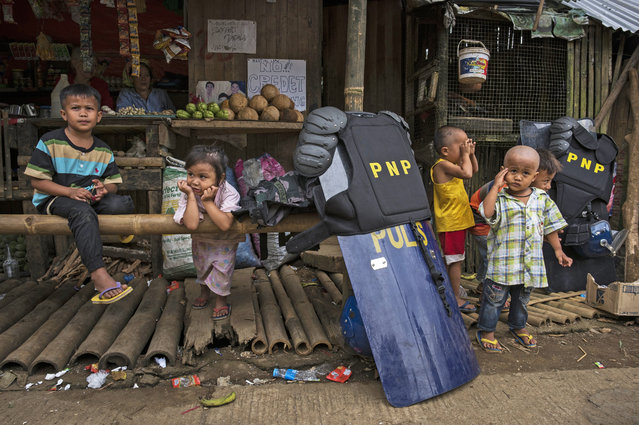 Police gear and shields are placed near playing displaced Marawi children on July 24, in Saguiaran, Lanao del Sur, southern Philippines. Evacuees report of worsening conditions inside evacuation centers, as well as their dificulty adjusting to cultural differences. They call on the government to end martial rule and the bombing of Marawi and let their traditional leaders and ways handle the thwarting of militants from their city. The Philippine Congress voted on Saturday to extend martial law in the southern part of the country since it was imposed to crush a rebellion by Islamic State-inspired militants. The decision was made two days before President Rodrigo Duterte delivers his annual state of the nation address as analysts have reportedly said Mr. Duterte appears to be using the crisis in Marawi as an excuse to impose authoritarian rule in the Philippines. (Photo by Jes Aznar/Getty Images)