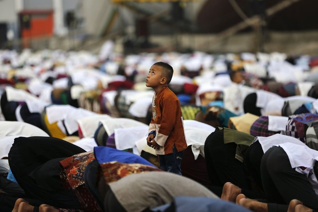 A boy watches a remote-controlled camera fly above (unseen) during a prayer session on Eid al-Fitr at Sunda Kelapa port in Jakarta July 28, 2014. Indonesia, which has the world's largest Muslim population, celebrates Eid al-Fitr with mass prayers and family visits to mark the end of the Muslim holy fasting month of Ramadan. (Photo by Darren Whiteside/Reuters)