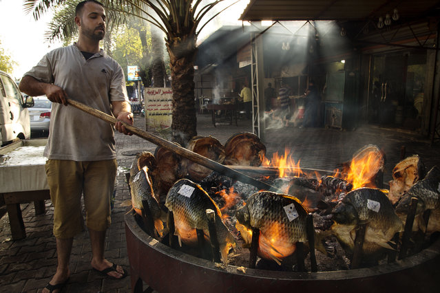 An Iraqi man cooks traditional Masgouf fish on a barbecue for sale in the Karada market July 02, 2014.  Masgouf, one of the national dishes of Iraq is a grilled carp seasoned with olive oil, rock salt, tamarind and ground turmeric. (Photo by Scott Nelson for the Washington Post)