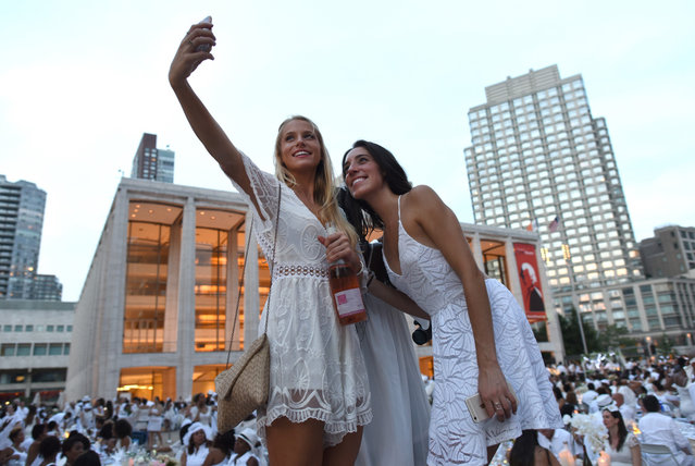 Guests attend the annual New York City Diner en Blanc, August 22, 2017 held this year at the plaza at Lincoln Center. (Photo by Timothy A. Clary/AFP Photo)