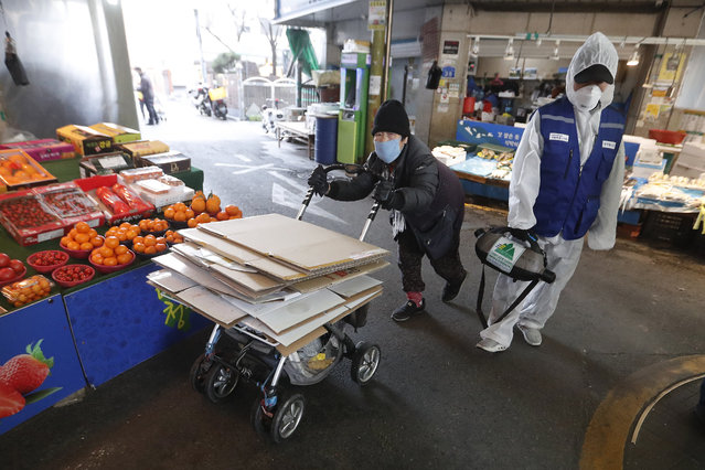A workers wearing protective gears sprays disinfectant as a precaution against the coronavirus at a market in Seoul, South Korea, Monday, February 24, 2020. (Photo by Ahn Young-joon/AP Photo)