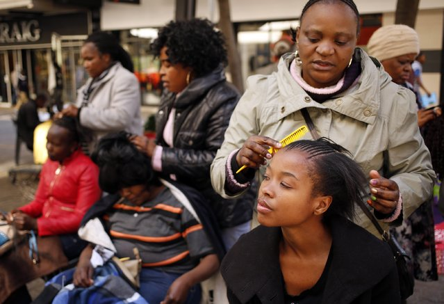 """Hairdressers attend to clients in downtown Johannesburg, August 5, 2014. This does not include sales from more than 40 other sub-Saharan countries, or the huge """"dry hair"""" market of weaves, extensions and wigs crafted from everything from synthetic fibre to human or yak hair. (Photo by Siphiwe Sibeko/Reuters)"""