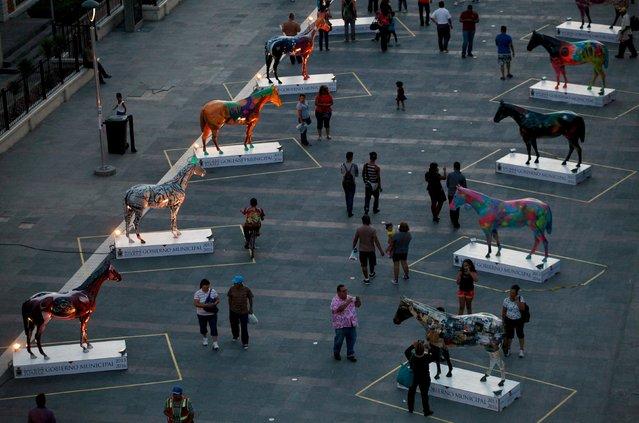 People walk near sculptures of fiberglass horses in downtown Ciudad Juarez, Mexico, August 25, 2015. (Photo by Jose Luis Gonzalez/Reuters)