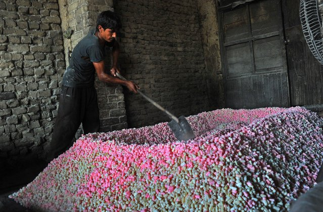 An Afghan confectionery worker makes traditional sweets at a factory on the outskirts of Jalalabad in Nangarhar province on August 11, 2014. Afghanistan's economy has improved significantly since the fall of the Taliban regime in 2001 largely because of the infusion of international assistance. Despite significant improvement in the last decade the country is still extremely poor and remains highly dependent on foreign aid. (Photo by Noorullah Shirzada/AFP Photo)
