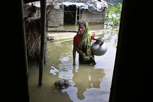 A woman walks through flood-affected houses in Burhaburhi village, about 70 (44 miles) east of Gauhati, India, Thursday, August 19, 2014. Floodwaters are receding in some areas but authorities said they had to be vigilant against water-borne diseases. (Photo by Anupam Nath/AP Photo)