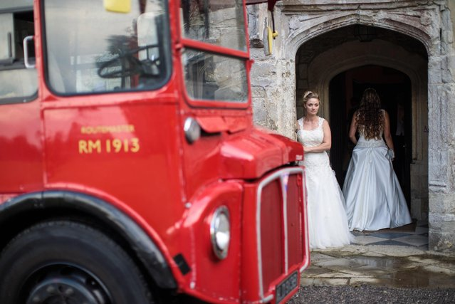 A Routemaster bus is parked outside as debutante Lauren Evans, 27, from Haslemere, looks out of the entrance to Boughton Monchelsea Place ahead of the Queen Charlotte's Ball on September 9, 2017 in Maidstone, England. (Photo by Jack Taylor/Getty Images)