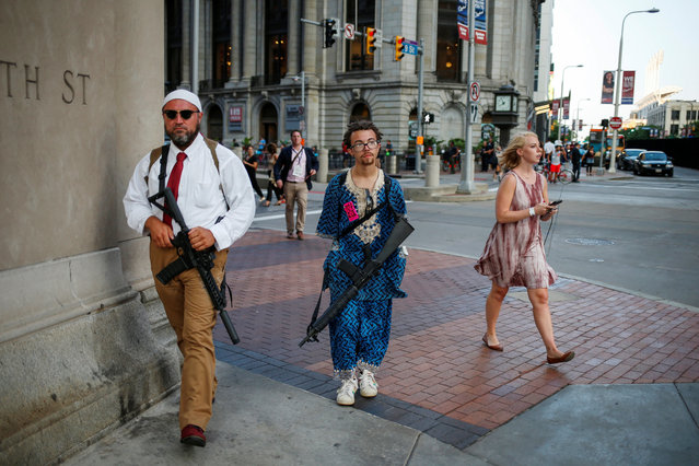 A woman walks past Micah Naziri and Jaimes Campbell, advocates for open carry, as they patrol the streets of Cleveland with their assault weapons during the Republican National Convention in Ohio, U.S., July 19, 2016. (Photo by Adrees Latif/Reuters)