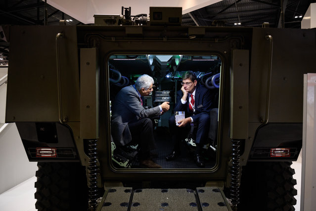 Two men talk as they sit inside a VBCI amoured personel carrier at the DSEI event at the ExCel centre on September 12, 2017 in London, England. The annual weapons and security trade fair sees manufacturers of all aspects of military, naval, airforce and security from all over the world display their latest designs to delegates. (Photo by Leon Neal/Getty Images)