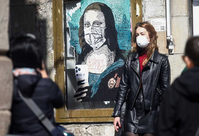 "A masked tourist poses for a souvenir photo next to a graffiti titled ""Mobile World Virus"" depicting ""La Gioconda"", aka Mona Lisa, with a mobile phone and a medical mask, by urban artist TVBoy, close to the Sant Jaume square in Barcelona, Spain, 09 March 2020. Barcelona's Deputy Mayor and two town councillors are in quarantine after they were in contact with a City Hall's worker who was tested positive for the COVID-19 coronavirus. (Photo by Quique Garcia/EPA/EFE)"