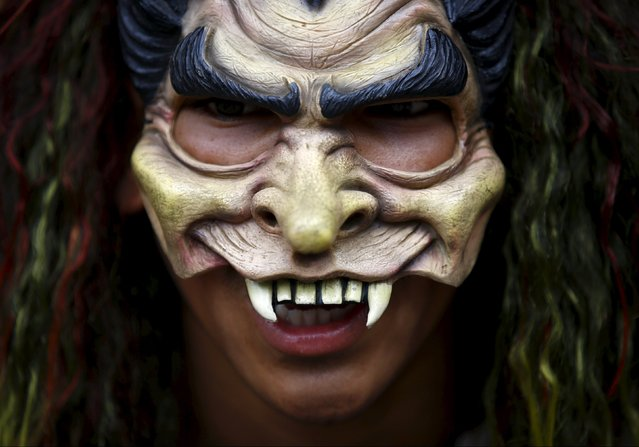 A masked devotee takes part in a parade commemorating the Neku Jatra-Mataya festival, the Festival of Lights, in Lalitpur, Nepal August 31, 2015. Devotees celebrate the Buddhist festival which marks the victory of Sakyamuni Buddha over Mara, by praying for the souls of departed family members and holding parades throughout the city. (Photo by Navesh Chitrakar/Reuters)