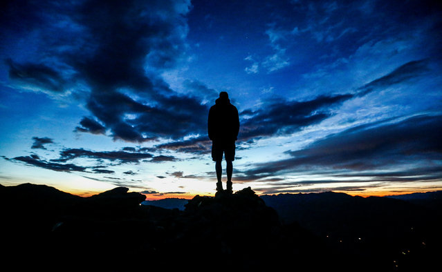 A man stands during sunrise on Kreuzjoch mountain in the Zillertal Alps in Schwendau, Austria July 11 2016. (Photo by Dominic Ebenbichler/Reuters)