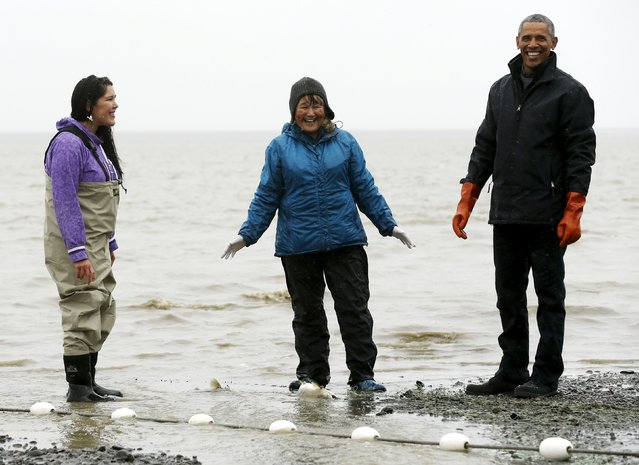 U.S. President Barack Obama (R) laughs after a fish relieved itself on him while he meets traditional fishermen on the shore of the Nushagak River in Dillingham, Alaska September 2, 2015. (Photo by Jonathan Ernst/Reuters)