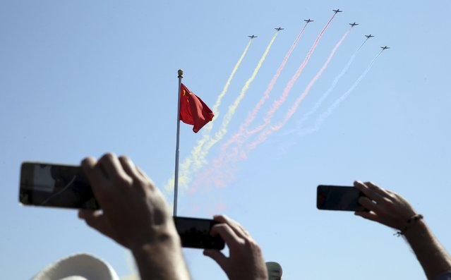 People record trainer jets flying over Tiananmen Square during a military parade to mark the 70th anniversary of the end of World War Two, in Beijing, China, September 3, 2015. (Photo by Reuters/China Daily)