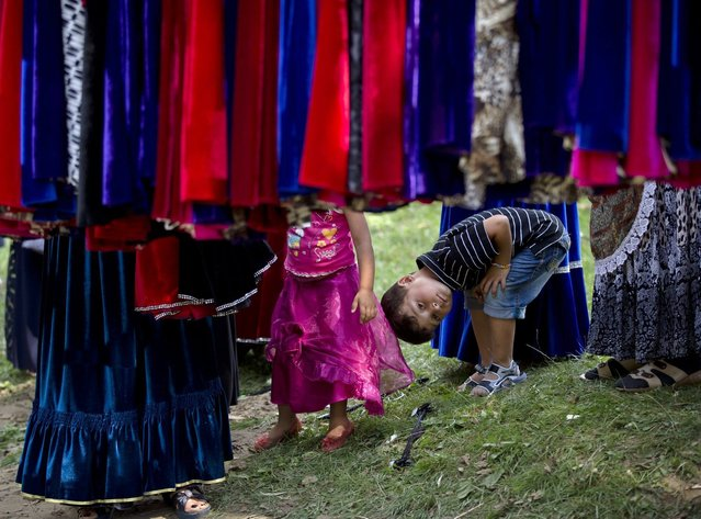 A Roma boy watches as women look at skirts while the Roma community celebrates the Birth of the Virgin Mary in Costesti, Romania, Monday, September 8, 2014. (Photo by Vadim Ghirda/AP Photo)