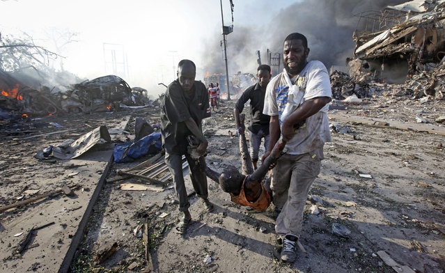 Somalis remove the body of a man killed in a blast in the capital Mogadishu, Somalia Saturday, October 14, 2017. (Photo by Farah Abdi Warsameh/AP Photo)