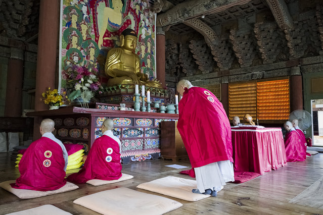 """Monks hold evening chanting ceremony in The Mail Hall of Seonamsa Buddhist Temple on July 31, 2015 in Suncheon, Jeollanamdo Province, South Korea. The temple was founded in A.D. 529, and the name Seonam means """"Heavenly Rock"""" or """"Immortal's Rock"""". The Main Hall of the temple is one of treasures of South Korea. (Photo by Shin Woong-jae/The Washington Post)"""