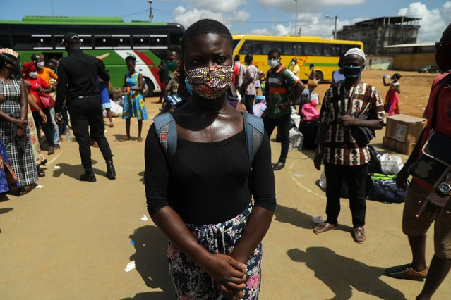 A student waits to board a government chartered bus convoy, which will take students and teachers back to cities and schools of the countryside, as the lockdown due to the coronavirus disease (COVID-19) is eased, in Abidjan, Ivory Coast on May 19, 2020. (Photo by Luc Gnago/Reuters)