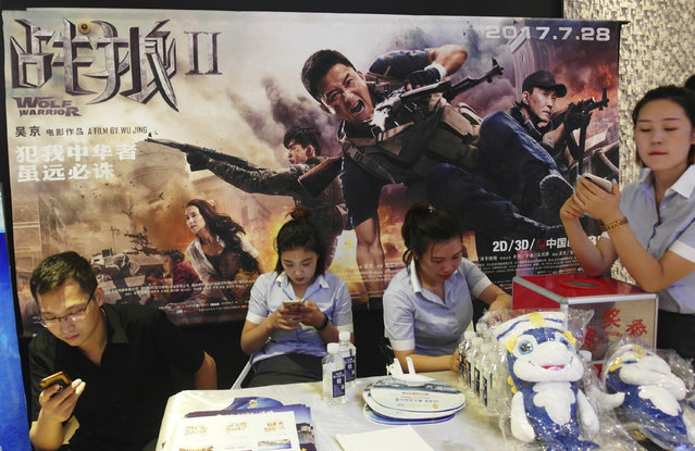 """In this August 20, 2017, photo, cinema workers wait for customers in front of a poster for the movie """"Wolf Warriors II"""" in Yichang in central China's Hubei province. In this summer's """"Wolf Warrior II"""", Chinese action star Wu Jing portrays a tough super-patriot who rescues both fellow countrymen and oppressed Africans with help from the People's Liberation Army and became China's biggest-grossing movie ever. This red-blooded nationalism has been channeled skillfully by President and ruling Communist Party leader Xi Jinping as he seeks to strengthen the party's role in Chinese life and shepherd the country's rise to prominence at a time when the United States and others in the West are seen to be in retreat. (Photo by Chinatopix via AP Photo)"""