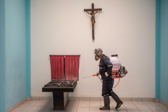 A worker disinfecta an area of El Angel crematorium, in Lima on May 21, 2020. Peru has become the second Latin American country after Brazil to reach 100,000 coronavirus cases, according to health ministry figures out Wednesday. (Photo by Ernesto Benavides/AFP Photo)