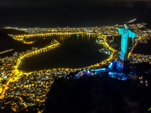 Christ the Redeemer statue is illuminated with the projection of a health worker's uniform during a religious ceremony to celebrate Easter Sunday, on Mount Corcovado, Rio de Janeiro, Brazil, 12 April 2020. (Photo by Antonio Lacerda/EPA/EFE)