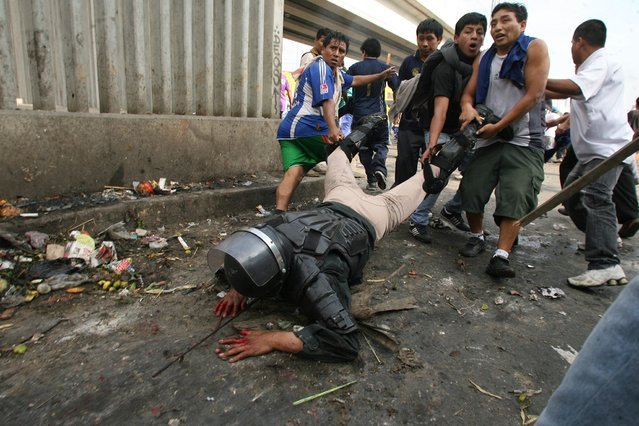 Protesters drag a riot police officer who was knocked off his horse with rocks thrown by workers of 'La Parada' wholesale market in Lima, Peru, on October 25, 2012. Clashes between the wholesale market workers and police officers left two people dead and more than 100 injured. (Photo by Alessandro Currarino/Diario El Comercio/Reuters)