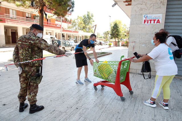 A woman delivers a cart with food for people in quarantine at a residential complex, after 49 people tested positive for the coronavirus disease (COVID-19) and the area was cordoned off, in the village of Mondragone, northwest of Naples, Italy, June 26, 2020. (Photo by Ciro de Luca/Reuters)