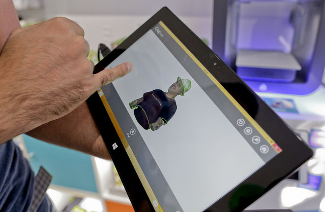 In this August 14, 2014 photo, Cubo toy store owner Victor De Los Angeles shows the results of a 3-D scan of Kevin Micelli on a tablet after scanning him with a Sense 3-D scanner at his store in New York. (Photo by Julie Jacobson/AP Photo)