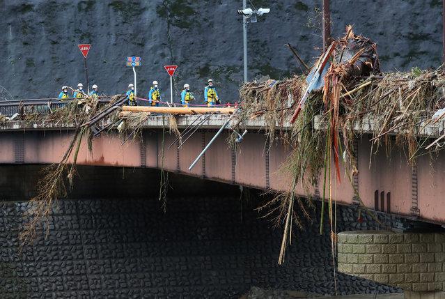 Aid workers walk through debris on Kuma bridge following torrential rain in Kuma, Kumamoto prefecture on July 7, 2020. (Photo by JIJI Press/AFP Photo/Stringer)
